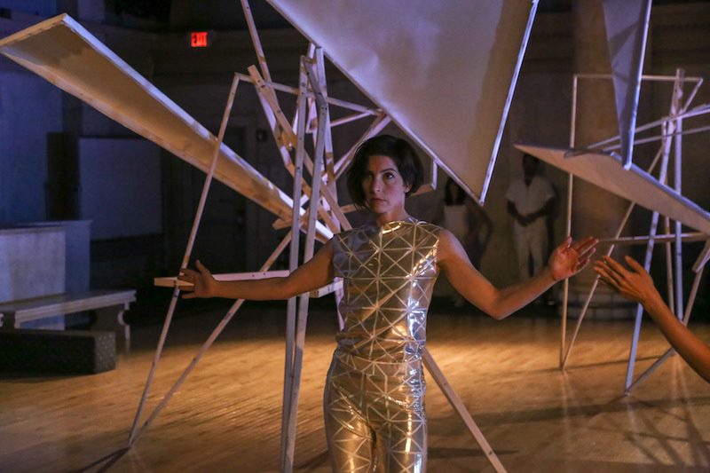 Laura Peterson in a gold lamé fabric top and pants in front of the geometric tepee-like installation