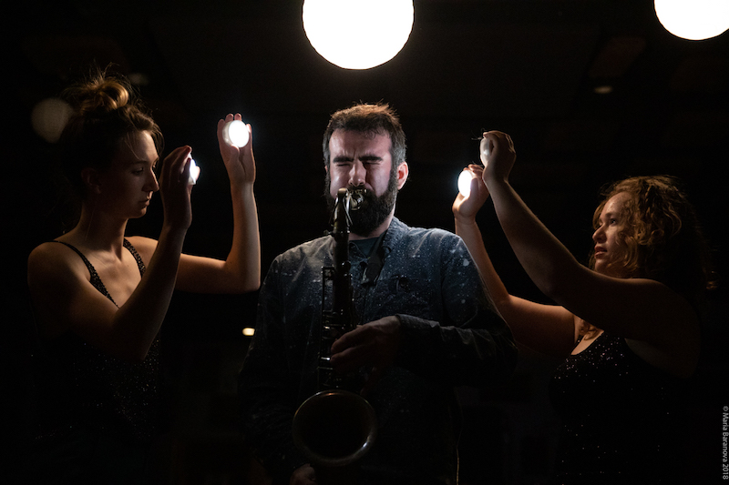 Two women hold lights while one man blows into a saxophone