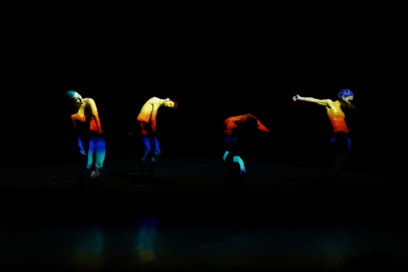 Four dancers stand in a line curving their torsos. A rainbow-colored light is projected on their bodies.