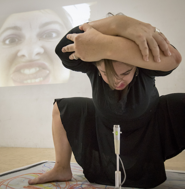 Anabella squats around a camera. She wraps her arms around herself. A film of her face is projected on the wall behind him.