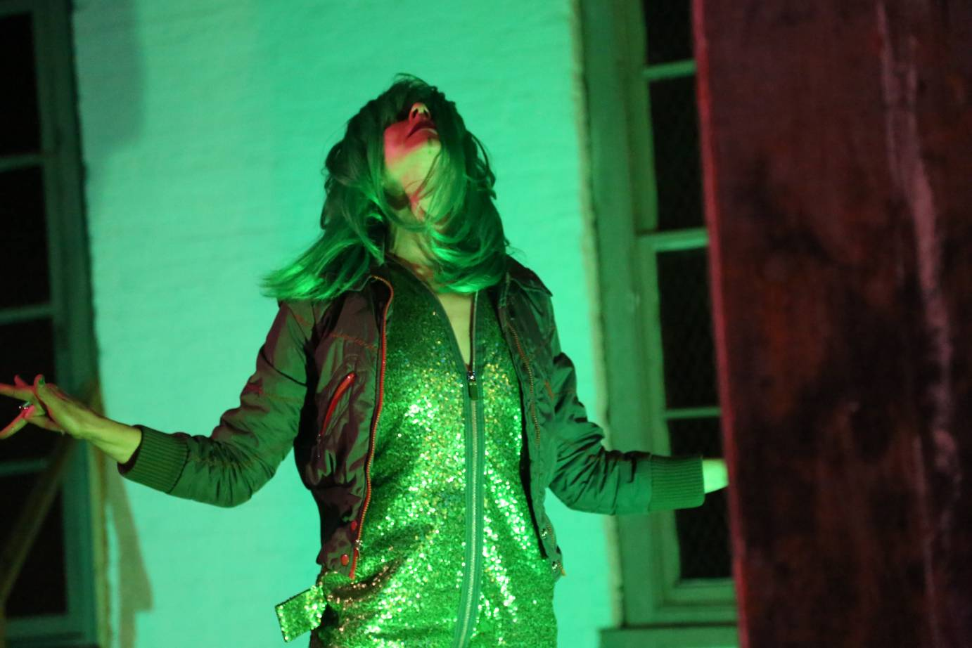 A woman in a green wig throws her head back