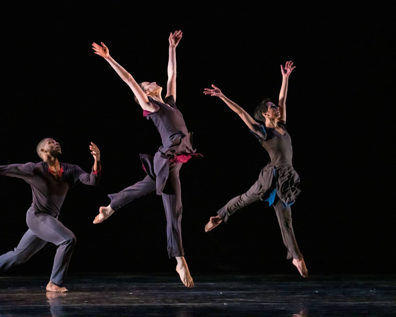 Two dancers leap to heaven, their arms extended, as one man runs behind them