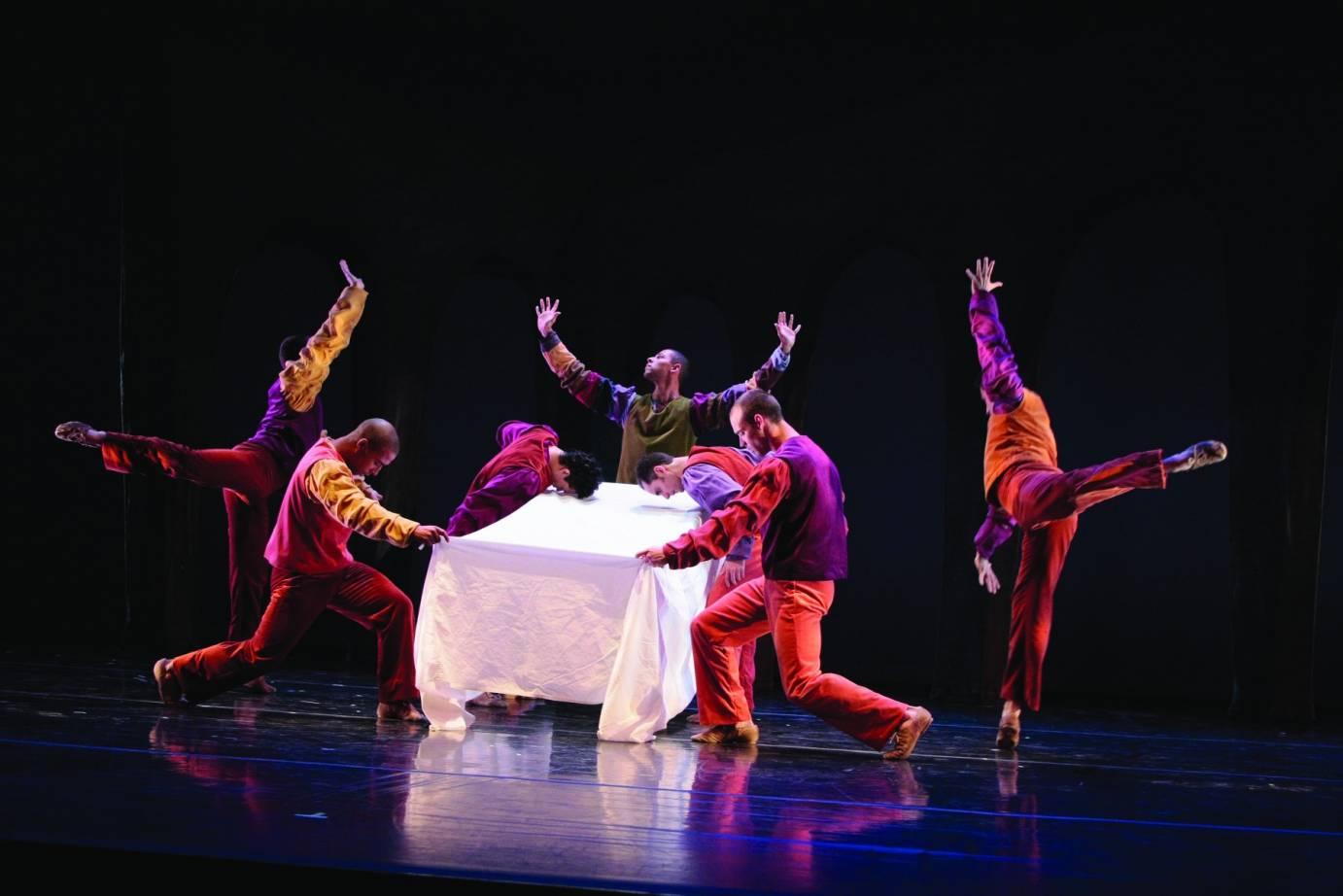 Male dancers dressed in reds, yellows and purples cluster around a table with a white tablecloth