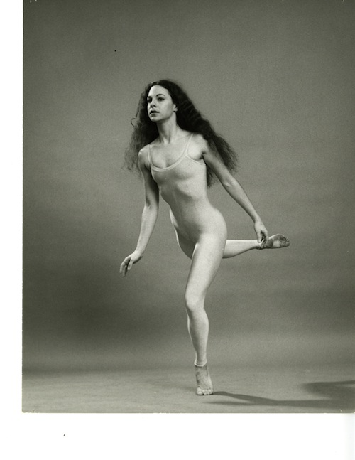 Carla Maxwell with her hair dwn in shimmery unitard perched on the ball of a foot as if she is floating in the air