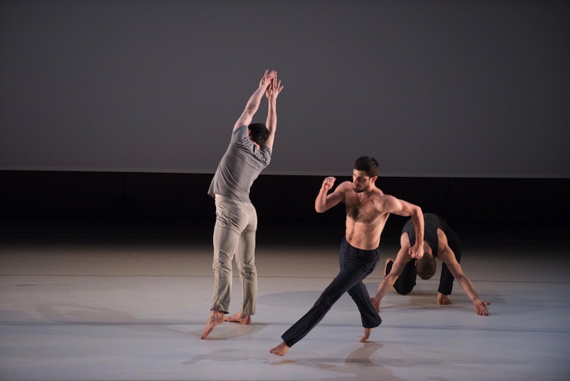 A trio of men dance center stage; each performing their own solo. One is kneeling on the ground, while the other is in mid-run and the other stretches both arms upwards toward the ceiling