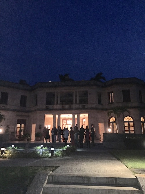 People mingling outside of the U.S. Residence in the evening
