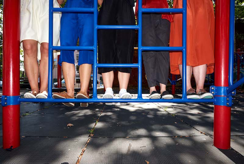 Five individual's feet stand on blue playground bars