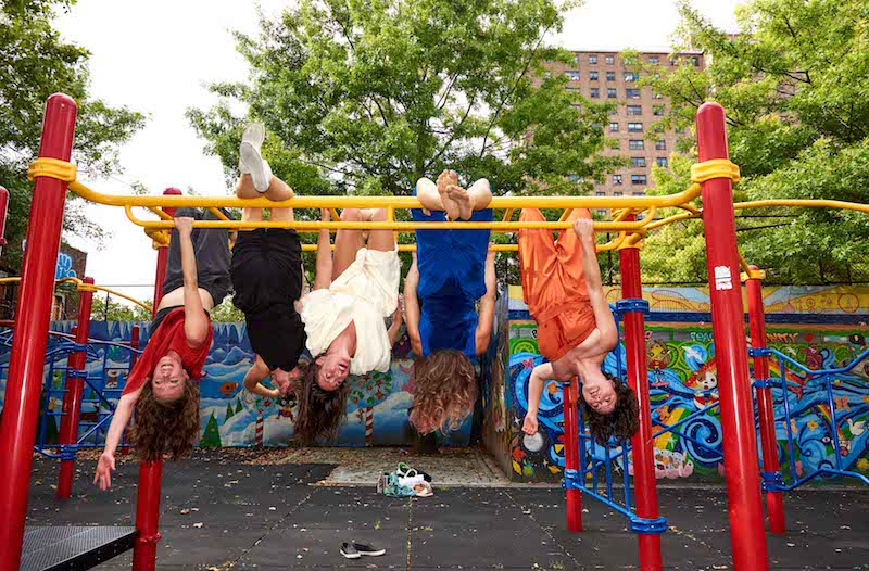 The five members of the Lovelies hang upsidedown from yellow monkey bars in an outdoor playground