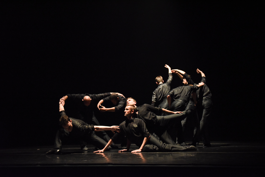 Men wearing all black curve their arms, some lunge to floor, and others bend their arms above their head with their backs facing the audience.