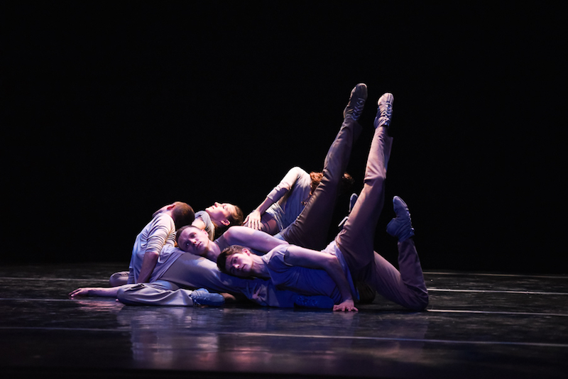 Dancers lay on one another in cascading heap on stage. Two dancers lift their legs in attitude positions above their heads.
