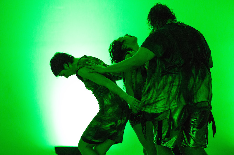 3 dancers in a tight formation cast in bright green light