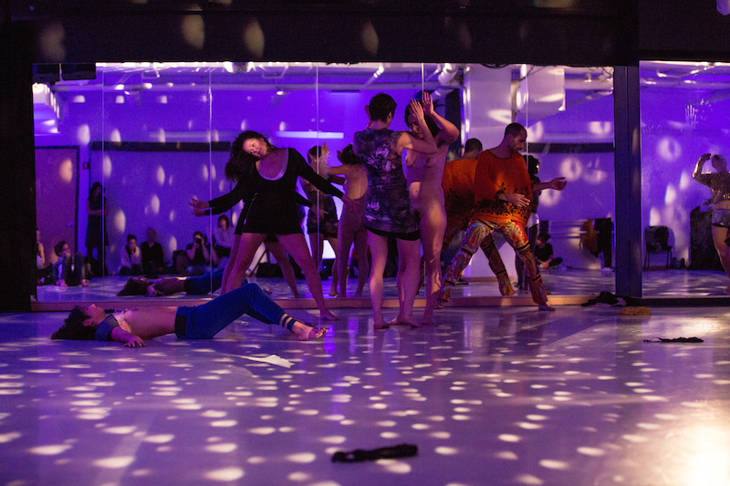 A mass of performers dancing against a mirror under a disco ball and purple lights