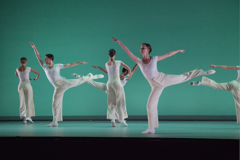 Dancers all in white execute expansive arabesques in front of a sea green background