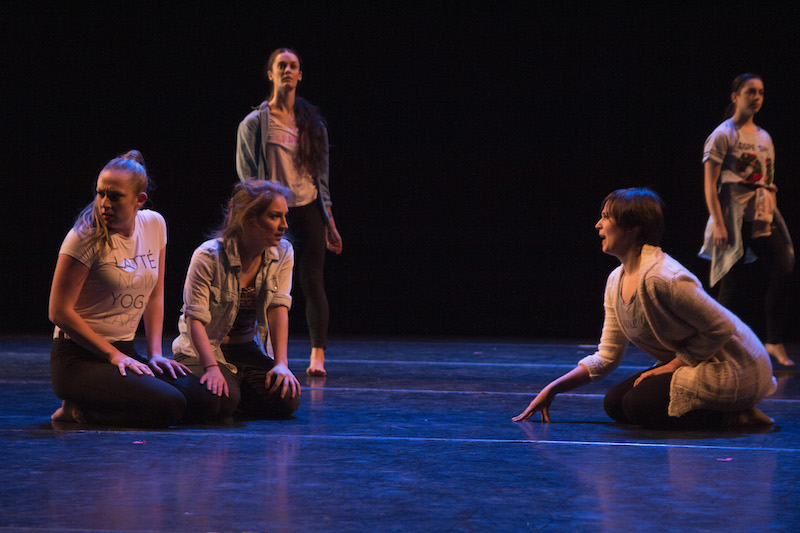 Young girls in rehearsal clothes sit on the floor and stand in the background and appear to be looking for something