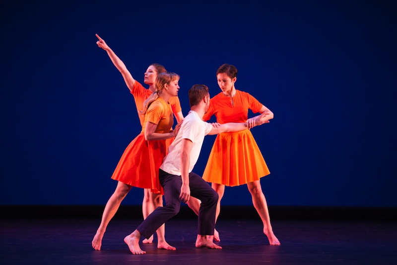Three women in orange dresses cluster around a man, one pulls his arm while looking intently at him