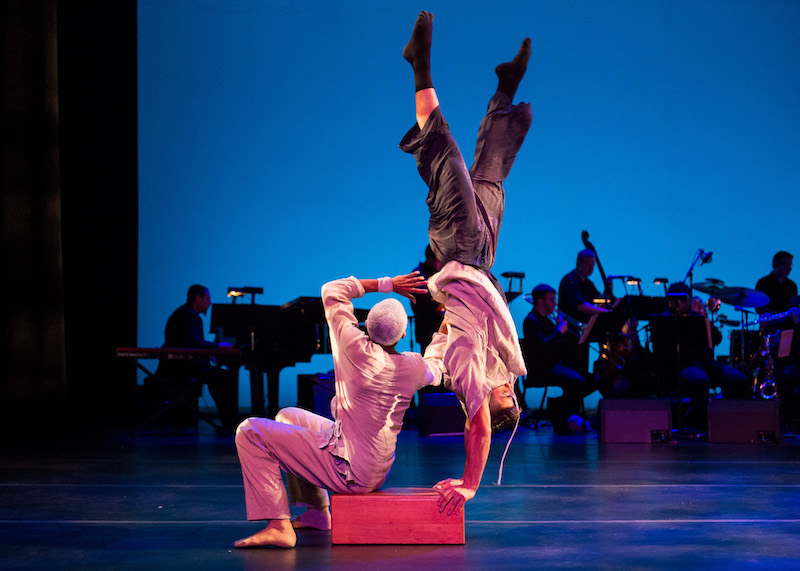 A man sits on a wooden box as another dancer does a hand stand off of it. The band is in the background.