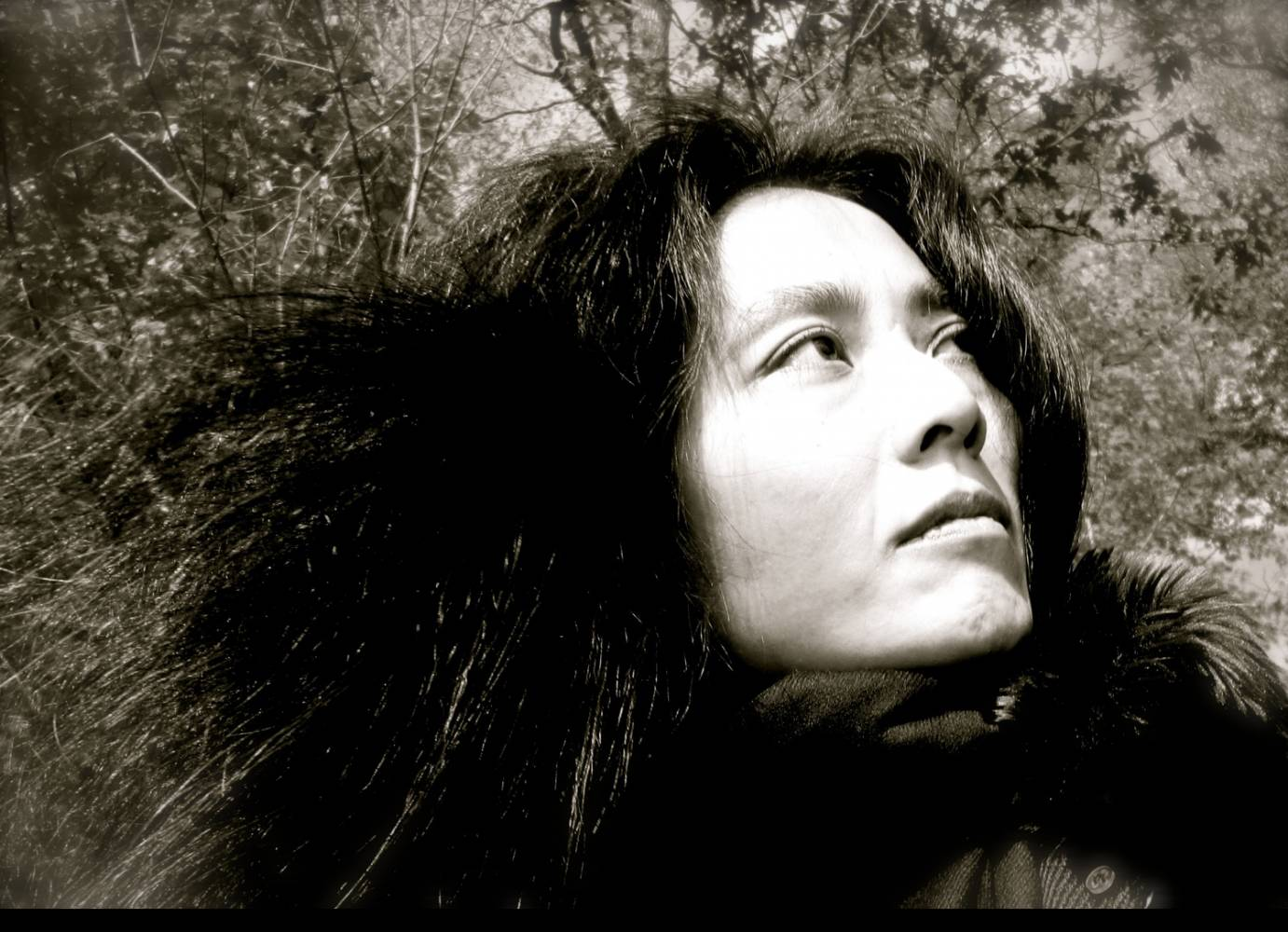 a black and white portraite of Mana Hashimoto outside in the daytime,among leaves, in a forest type setting. She faces on a high diagonal, and her hair seems wild like the twigs and branches around her
