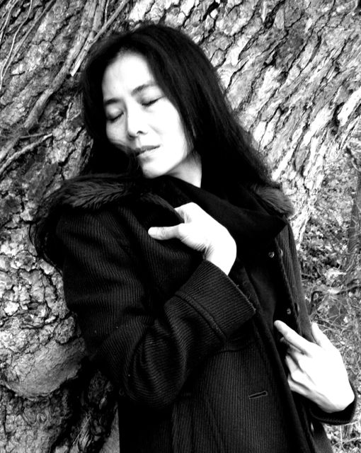 a black and white portrait of Mana Hashimoto leaning against the bark of a big tree, her eyes are closed and her hands cling to her jacket, it is as if the tree comforts her