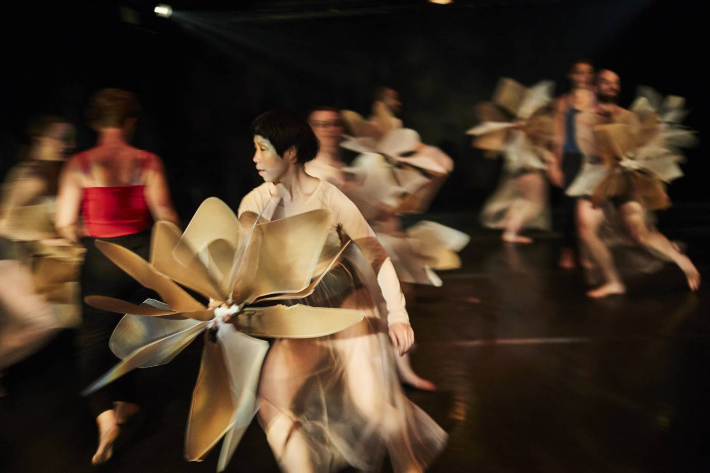 Dancers hold pinwheels as they run