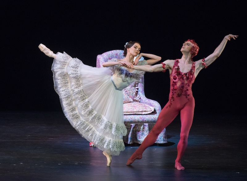 A ballerina in an ankle length white ruffled dress extends behind her while she holds the hand of her partner in a rose unitard