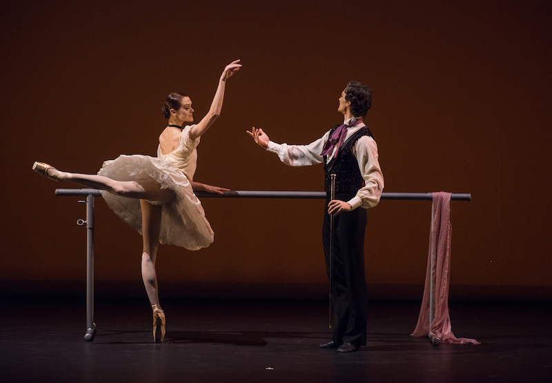 Lopatkina holds onto a ballet barre as she balances en pointe in attitude her partner gestures his hand to her.