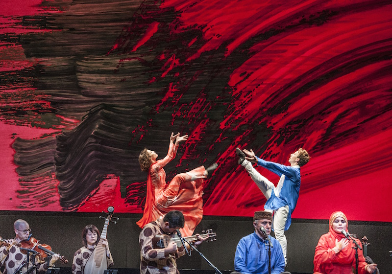Two dancers lift their legs high into the air. Musicians are in the foreground while an abstract black and red mural hangs behind them.