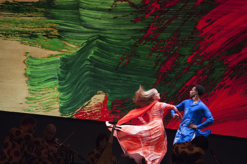 A man in a blue tunic swings a woman in a coral dress by the arm. Her blond hair blows behind her.