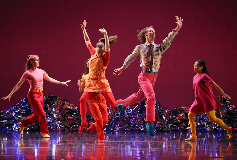 A group of dancers in hues of pink and orange skip and leap