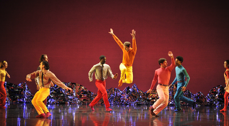 A dancer in orange and yellow leaps high into the air while other dancers, some in turtlenecks and others in ties, move around the solo jumper.