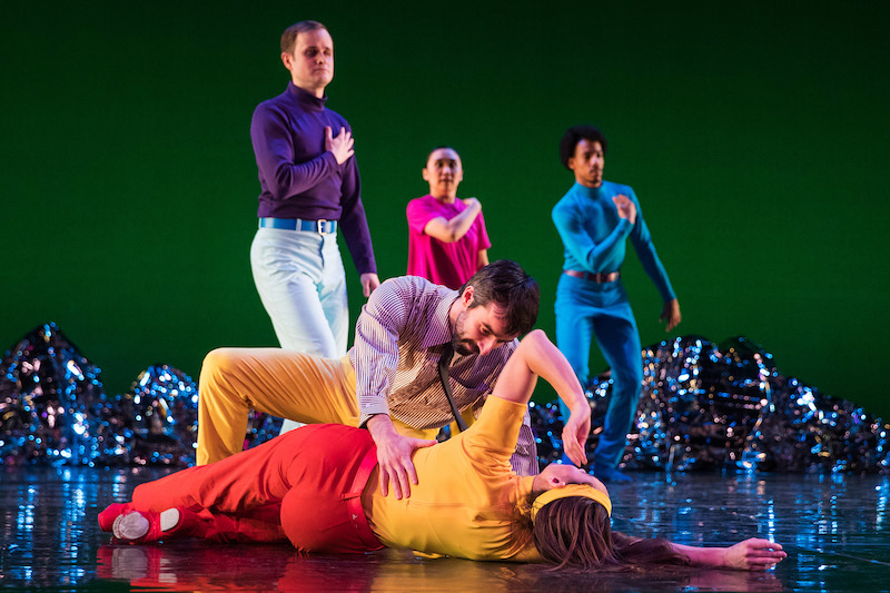 Three dancers in neon hues cross their hands over their hearts. While a couple in the foreground crouch to the floor.