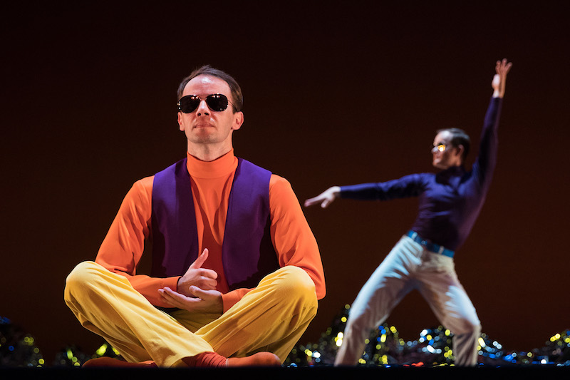 A man in sunglasses sits cross-legged in the foreground. A dancer in a purple turtleneck poses in the background.
