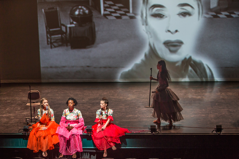 Three women in brightly colored dresses sit on the edge of the stage. One woman talks into a microphone. Xin Ying, in a grey colored dress stands to the right of them holding a microphone stand. A projection of Martha Graham is in the background.