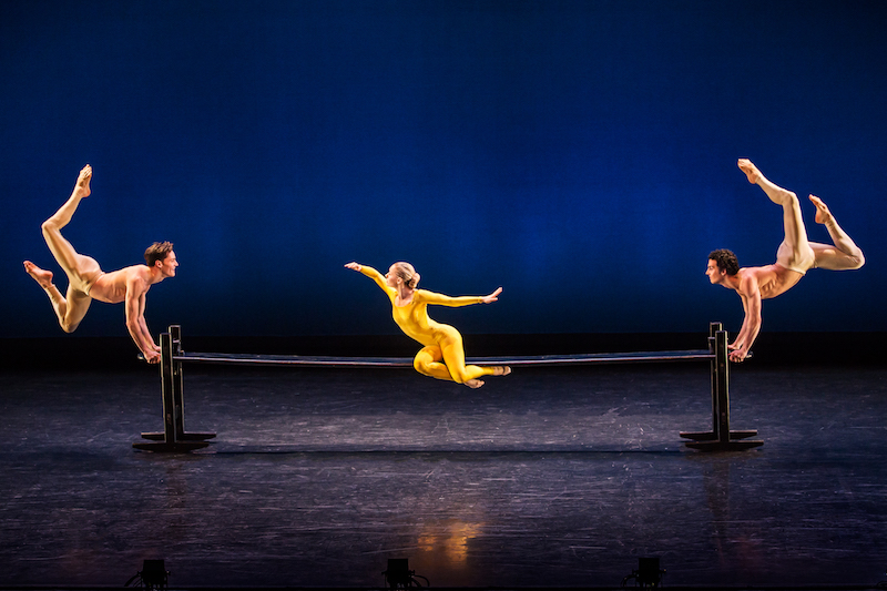 A woman in a yellow unitard sits on a wooden plank. Two men leap into the air, holding onto to each of the plank's ends. Their backs arch and their feet point to the ceiling.