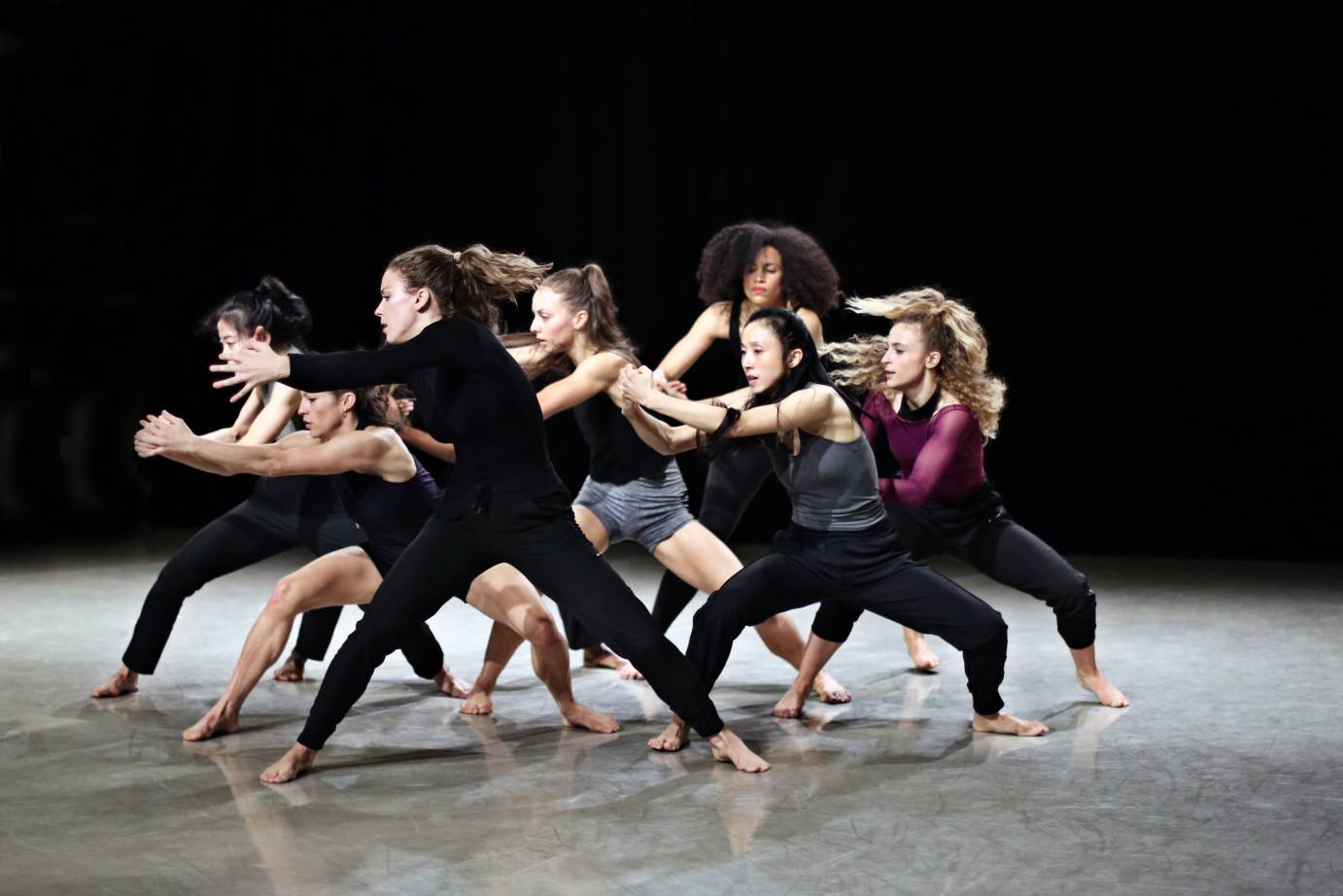 Group of female dancers clasp their hands while looking fierce