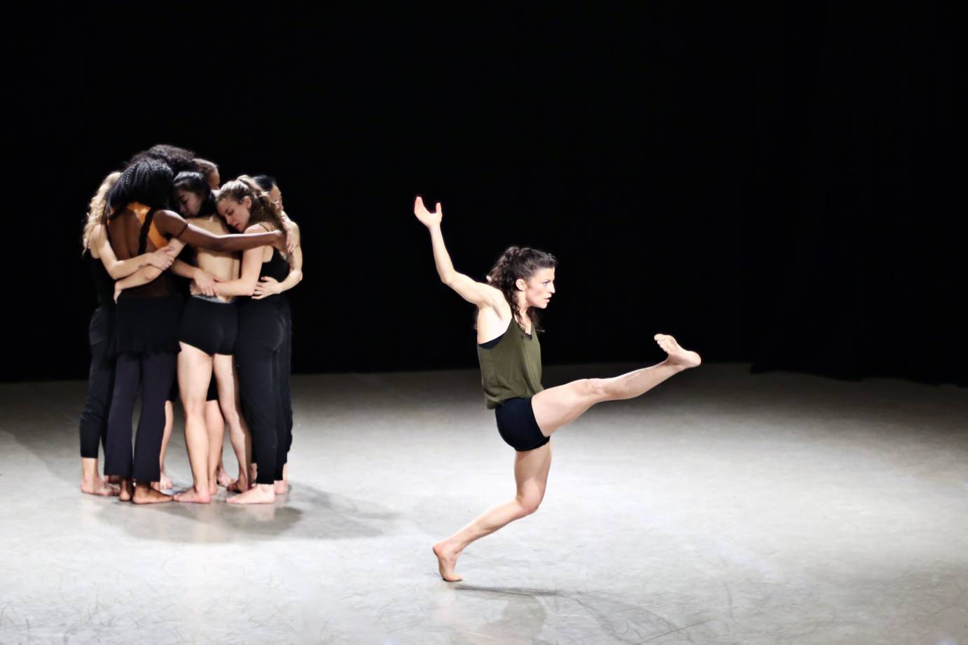 One solo dancer kicks while a group of women hug in the background