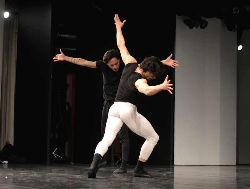 Two men open their arms and lunge toward each other. They wear black and white t-shirts and ballet tights.