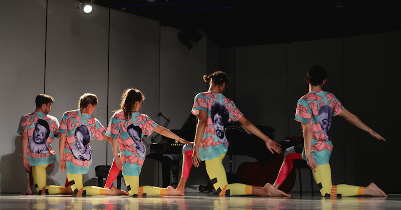 A group of dancers in color leggings and tees kneel in a straight line. their right arms extend on a low diagonal.
