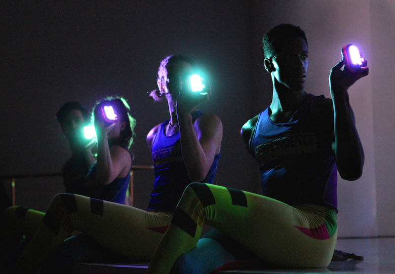 Three dancers in blue tank tops and yellow neon leggings shine lights in front of their faces