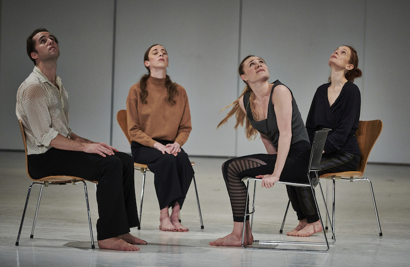 Four dancers sit in chairs with metal legs. Three look towards the ceiling and another tranquilly closes her eyes.