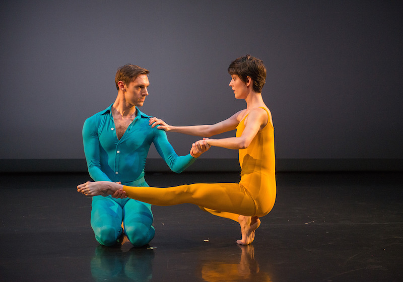 Benny Olk, in a bright blue unitard with buttons up the front and collar, kneels and holds Vanessa Knouse's hand and ankle as she assumes a squated position in which her left leg extends in front of her.