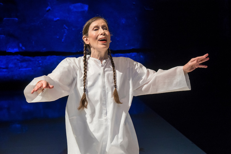 Meredith Monk, in a white caftan and her hair in two braids, sings with her arms out to her sides.