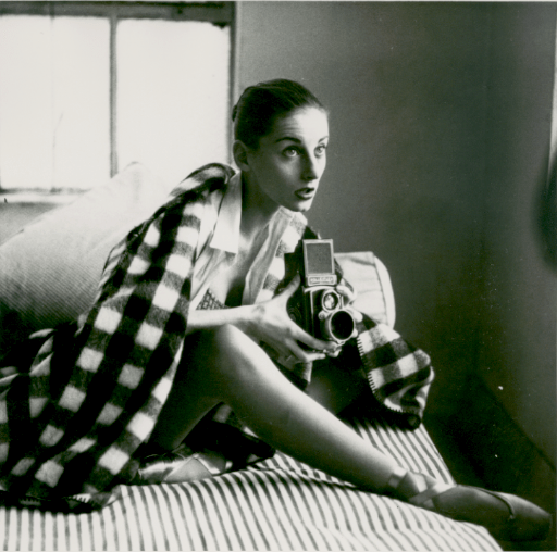Tanaquil Le Clerq sitting on a bed with the covers pulled up around her and holding a polaroid camera.