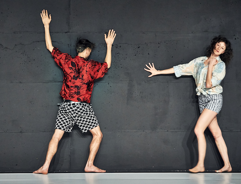 Two dancers in geometric-printed shorts and tropical button ups lean against a concrete wall for support.