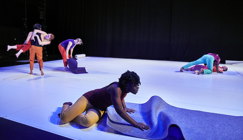 A woman sits in the foreground and rolls out a purple mat. Couples in the background pick one another up or lean over one another. One woman rolls up a mat.