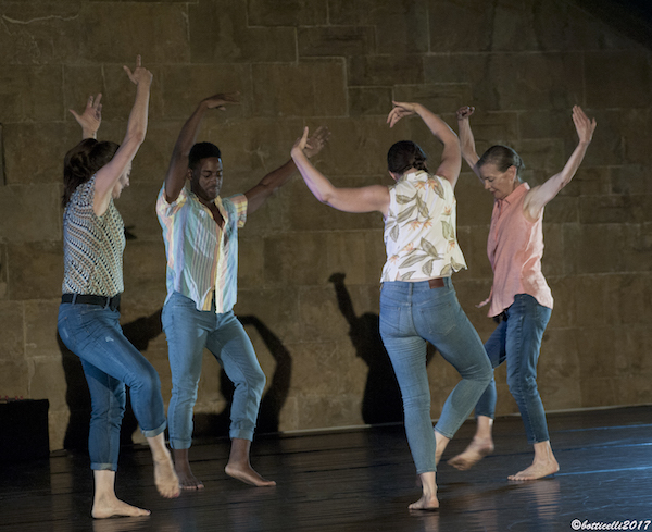Molissa Fenley and three dancers stand in a circle with their arms stretched above their heads. She wears jeans and colorful patterned shirts.