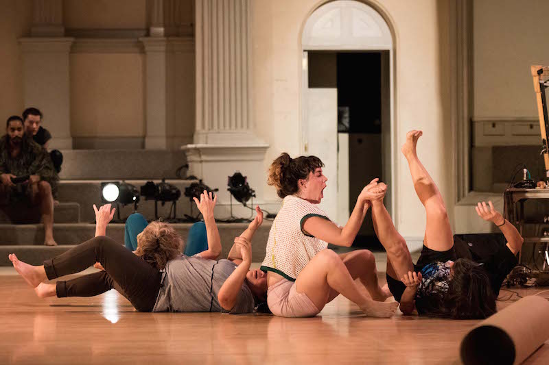 four dancers lay in various positions on the ground in a line