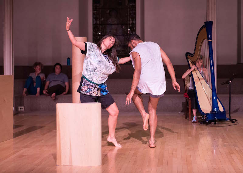 Wooden triangles and tubes are scatted. Two dancers stand around them. One is balancing on one leg