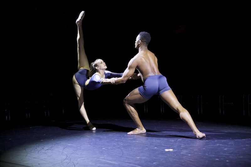 David Freeland in purple trunks supports Stephanie Williams by the arms as she extends her legs in a 180 degree arabesque