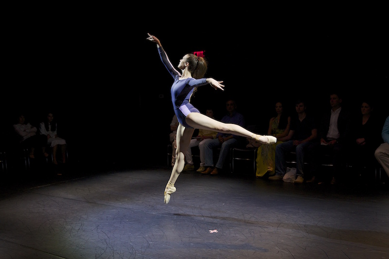 Stephanie Williams wearing a purple leotard executes a pristine arabesque sote. The photo captures her in mid air.