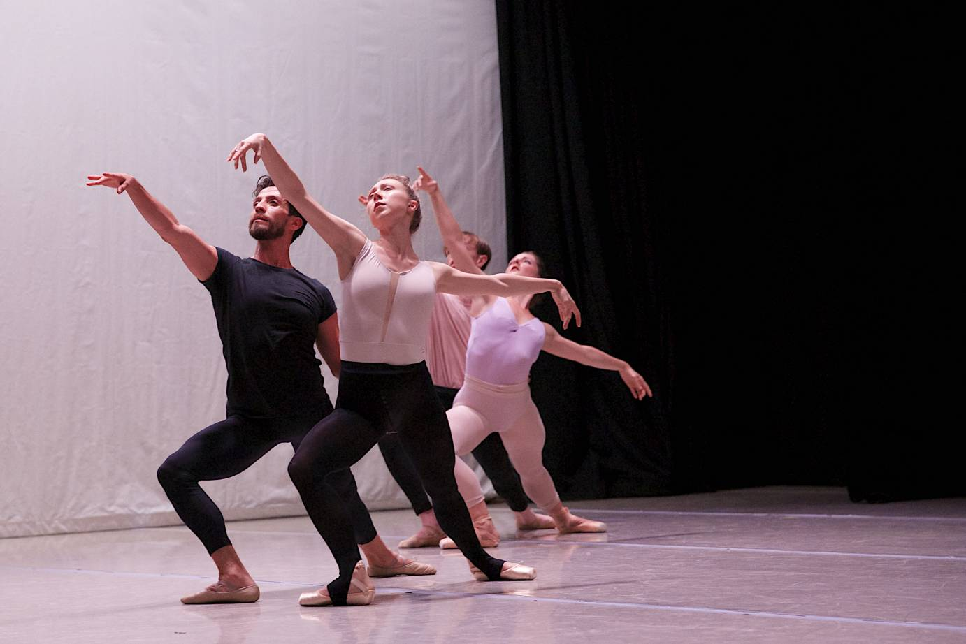 Four people in ballet practice clothes lunge with arabesque arms
